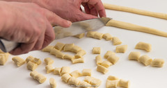 Cutting rolled trofie dough strings. (annick vanderschelden) Tags: italianfood bleached bread carbohydrates cereal chopping cooking culture cutting dough durum durumwheat filled flour foods gluten grains grinding half hand ingredient kitchenboard kitchenknife kneading macaroniwheat mixing oliveoil pasta pastawheat pasties pointofview polysaccharides powder protein raw rolled rolling semolina staple string trofie volcano water wet wheat belgium