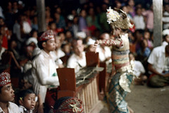 26-409 (ndpa / s. lundeen, archivist) Tags: nick dewolf nickdewolf 26 reel26 color photographbynickdewolf 1972 1970s film 35mm bali indonesia indonesian balinese traditional dance dancing performance dancer people spectators onlookers audience stage youngwoman child children kids girl costume clothing headdress musicians gamelan musician blurry outoffocus flowers oceania southpacific pacificislands culture pacificislandculture blur