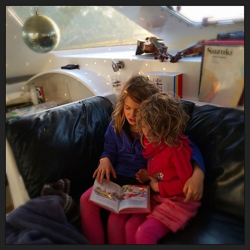 197/365 • these are a few of my favourite things :: Z reading to DB after D fell over in the driveway and scraped her hip and hands - when this sibling thing is working, it's so lovely • #197_2015 #sisters #smalls #7yo #4yo #Winter2015 #reading #mirrorbal