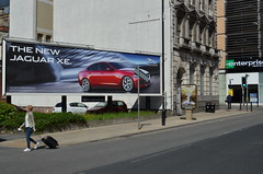 The Jaguar XE, Piccadilly, Manchester. (westport 1946) Tags: england architecture manchester unitedkingdom streetphotography piccadilly pedestrians architektur suitcase adverts streetadvertising jaguarcars carposter manchesterstreets jaguarxe