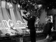 nocturnal market 09 (byronv2) Tags: edinburgh edinburghbynight edimbourg scotland blackandwhite blackwhite bw monochrome peoplewatching candid street night nuit nacht princesstreet princesstreetgardens market stall kiosk festivemarket game ball woman asian playing