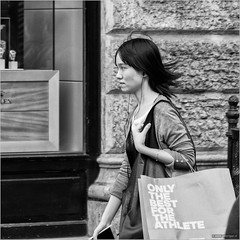 Only the best for the athlete (John Riper) Tags: johnriper street photography straatfotografie square vierkant bw black white zwartwit mono monochrome hungary budapest candid john riper fujifilm fuji xt1 18135 young woman lady girl athlete bag window rolex shop ears hearing earing things headphones iphone itunes music paper