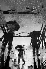 The Parallel Ethnicity (Shams Tabreez Niloy) Tags: street bridge people bw reflection water rain mobile umbrella phone group cellphone primo bnw walton cellphonograhy