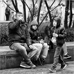 Life tastes good (John Riper) Tags: johnriper street photography straatfotografie square vierkant bw black white zwartwit mono monochrome netherlands candid john riper xt1 fuji 18135 men boys family drinking coke coca cola trees eye contact bench capuchon binnenwegplein