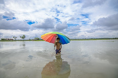 Life after the heavy rain. (Tapas Ghosh Photography) Tags: life sky india colors rain childhood clouds umbrella kid child flood journey monsoon horrible reflexion bengal flooded monsoonsky ranyday westbangal