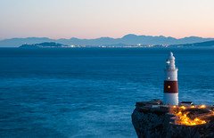 Europa Point Lighthouse, Gibraltar (Oliver J Davis Photography (ollygringo)) Tags: europe europapoint europa lighthouse cliff view strait straitofgibraltar gibraltar sea ocean atlantic medellin morocco africa ceuta spain mountains range ridge mountain coast coastline illuminated lights red white blue sky nikon d90 winter january 2017 long exposure rif clear continents continental divide meeting overseas territories territory colonies horizon land twilight connected distance travel trinity house