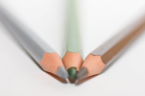 Trois crayons sur fond blanc