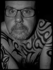 Tattooed chest. (CWhatPhotos) Tags: mono monochrome black white tattoo tattooed tattoos inked tribal chest shoulders selfee me photographs selfie have it photograph pics pictures pic picture image images foto fotos photography artistic that which contain digital cwhatphotos dark portrait body upper torso tatt ink pose face look beard olympus em5 mk ii prime lens warrior curved curves bodyart
