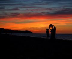 Make a wish. (Niesfornie) Tags: family pink friends light sea sky people orange black hot beach make contrast happy fly sand hands friend warm polska olympus baltic lucky lantern wish morze bałtyk chmury chmura chłapowo władysławowo
