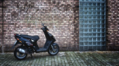 Parked (Anne Worner) Tags: anneworner ononesoftware ricohgr black brickwall chrome cobblestones exhaust glasswall layer mirror motorcycle parked seat street streetphotography texture wheels wideangle