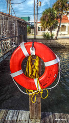 Life Saver (Chris C. Crowley- Gradually catching up- still bus) Tags: lifesaver lifepreserver ring round circle float ropes dock boathouse water riverbasin sky clouds palmtrees buildings architecture scenic bicycles wires powerlines transformer halifaxharbormarina