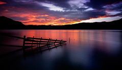 Creeping Fire (ajecaldwell11) Tags: dusk longexposure tutira hawkesbay newzealand sunset ankh norwester water foehn sky fence clouds caldwell laketutira light