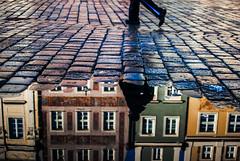 halves (ewitsoe) Tags: ewitsoe erikwitsoe nikon reflection puddle winter snowmelt city oldmarket poznan poland polska cityscpae split water pool man walking chilly 35mm