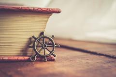 get the wheel and sail (Ayeshadows) Tags: ship steering wheel macro indoor book corner wood texture white curtains ahoy trinket nikkon