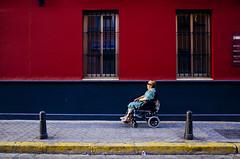 Sevilla, Spain (Pim Geerts) Tags: street old red woman photography vakantie sevilla wheelchair elderly gr rood ricoh spanje andalusie rolstoel straatfotografie websize pg031920