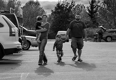 Americana (Szoki Adams) Tags: street family trees cars canon children outdoors parkinglot vermont shadows candid father mother streetphotography streetphoto casual protective suvs outing stalbans springtime sunnyday streetphotos strolling striding carryingchild szoki canong15 szokiadams