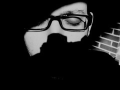 A Prism of Shadows: Self-portrait in Front of A Brick Wall (DerrickT) Tags: portrait blackandwhite white selfportrait black eye art glasses surreal hidden mysterious imagination greetings partial inshadows brickwallgoliath notsurreal filmformat