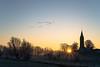 Last sunrise of the year (martinstelbrink) Tags: geese wildgeese gänse wildgänse blässgans blässgänse greaterwhitefrontedgoose greaterwhitefrontedgeese düffel schenkenschanz niederrhein nrw nordrheinwestfalen germany winter frost reif raureif ice kirche kirchturm church churchtower sony alpha7rii a7rii voigtländervmeclosefocusadapter zeissplanar50mmf20 zeiss carlzeiss planar 50mm f20 zm sunrise sonnenaufgang