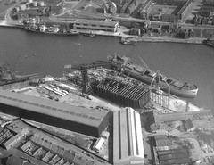 North Sands Shipyard and Corporation Quay, Sunderland (Tyne & Wear Archives & Museums) Tags: road roof shadow chimney abstract industry wall buildings landscape daylight construction cabin industrial pattern ship riverside crane piers ships engineering aerialview bank rail vessel row structure riverwear cranes deck maritime frame cylinder intriguing mast tradition shipyard northeast aerialphotography lindisfarne businesses digitalimage sunderland shipbuilding industrialheritage glassmaking coalmining orecarrier wearside twentiethcentury northeastengland blackandwhitephotograph pallion northsands georgeclark march1960 heavyindustries corporationquay coalstaithes wearmouthcolliery williamdoxfordsons austinpickersgill jlthompsonsonsltd sirjameslaingsons aerialtouroftheriverwear