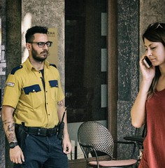 Strangers in Turin-Security guy (EiaOlaf) Tags: security guy street photography coglilattimo yellow cool tones lightroom canon nikcollection woman walking turin piazzasancarlo sancarlosquare bank analog life streetlife human people person man glasses tattos