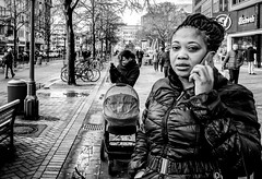 A close call. (Mister G.C.) Tags: blackandwhite bw ricoh ricohgr streetphotography urbanphotography candid street shot image photograph people monochrome town city young lady woman braids phone mobilephone cellphone telephone eyecontact closeup zonefocus zonefocusing snapfocus pointshoot mistergc schwarzweiss strassenfotografie hannover niedersachsen lowersaxony deutschland europe germany