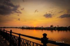 Riverbank Sunset (axxonlive) Tags: sunset cloud sun reflection yellow river haze horizon