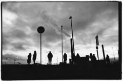 HELSINKI IS LONESOME (danieltim.net) Tags: blackandwhite industrial landscape cityscape skies grey clouds shadows silouettes darkroomprint silvergelatin dramaticsky finland europe winter humanelement urbanlife filmphotography