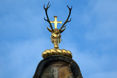 Antlers and Cross set above Canongate Kirk (Tony Worrall) Tags: scotland scottish north country place visit area county attraction open stream tour scots uk tourist edinburgh city capital centre street urban candid people person capture outside outdoors caught photo shoot shot picture captured picturesinthestreet crowds cross golden cool gold art head horns canongate kirk canongatekirk