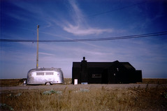black house, silver caravan (lomokev) Tags: blue house black cosina dungeness sliver trailer caravan cx2 file:name=bgen034