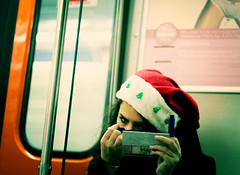 She's Beginning To Look A Lot Like Christmas (dzgnboy) Tags: toronto ttc subway santahat makeup fauxprolomo application dzgnboy img3425a 50mm f14 hipshot