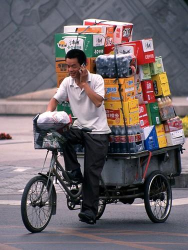 Un commerciante trasporta la sua merce per le vie di Pechino