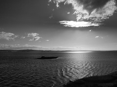 Sun Over the Water (cycle.nut66) Tags: light summer sky blackandwhite cloud sun nature water monochrome st island four waves cross jesus reserve olympus holy northumbria micro grayscale yeshua thirds evolt cuthberts jakedog epl1 mzuiko