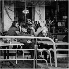 Babylon (John Riper) Tags: johnriper street photography straatfotografie square vierkant bw black white zwartwit mono monochrome netherlands candid john riper dordrecht canon 6d 24105 l couple old man lady terrace babylon eetcafe streetphotography cap warsteiner bag oil lamp fence