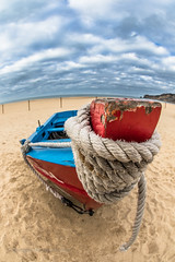 History on the beach (Howard Ferrier) Tags: sand fishingboat atlanticocean rope bow portugal dinghy paint blue beach ocean timber clouds feet red nazare sea europe marinevessel nazaré leiria pt