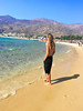 Not So Far Away (lost.mohican) Tags: man standing alone beach three quarter view tall lean long blond hair swept back shoulders black shorts hands pockets bare feet yellow sand blue water waves surf aegean sea cove mountains rocks sky sunlight sun summer warm bright wistful yearning