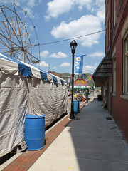 A carnival is installed downtown. (Tim Kiser) Tags: 2015 20150506 highway219 highway72 img8684 may may2015 parsons parsonshomecoming parsonshomecomingfair parsonsvolunteerfiredepartmenthomecomingfair parsonswestvirginia route219 route72 statehighway72 stateroute72 tuckercounty tuckercountywestvirginia us219 ushighway219 usroute219 walnutstreet westvirginia westvirginia72 westvirginiahighway72 westvirginiaroute72 awning banner barrels barrelsofsand blueplastic blueplasticbarrels brickpavers brickpaving carnival carnivaltent cumulus cumulusclouds decorativebanner decorativebrickpavers downtown downtownparsons easternwestvirginia electricline fair ferriswheel lamppost lightpole northernwestvirginia ornamentalbrickpavers overheadelectricline overheadpowerline partlycloudy paved pavement pizzastand plasticbarrels powerline sandbarrels shingledawning shingles sidewalk storefrontawning tarpaulins tarps whitetarpaulins whitetarps woodshingles woodenshingles unitedstates