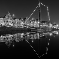 Pegasus (McQuaide Photography) Tags: haarlem noordholland northholland netherlands nederland holland dutch europe sony a7rii ilce7rm2 alpha mirrorless 1635mm sonyzeiss zeiss variotessar fullframe mcquaidephotography lightroom adobe photoshop tripod manfrotto light licht water reflection stad city urban waterside lowlight architecture outdoor outside waterfront building longexposure blackandwhite blackwhite bw mono monochrome square squarecrop 11 winter river spaarne riverside pegasus boat ship schip boot zeilboot sailboat traditional authentic night nacht nightphotography