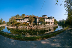 House along Naviglio Grande (Milan) (clodio61) Tags: europe italy lombardy milan navigliogrande turbigo autumn bicycle building canal color day exterior fall fisheye house outdoor pedestrian photography plant reflection sunny track water