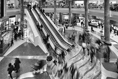 Mall Movement Mono (Mister Oy) Tags: davegreen oyphotos ©oyphotos traffordcentre intu monochrome mono blackandwhite fujixpro2 fuji1024mm fuji movement motion blur people shopping retail escalator diagonal stairs manchester greatermanchester trafford busy crowded mall shop store