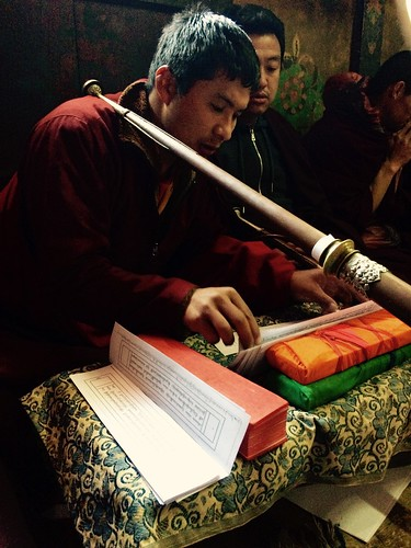 Buddhist monk checking his prayer notes during festival celebrations. Thimphu, Bhutan