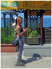 """""""Selecting her skating song"""" - PIran, Slovenia (TravelsWithDan) Tags: piran slovenia skating inlineskating woman uniquehair mohawk tattoos listeningtomusic candid outthewindow streetphotography outdoors"""