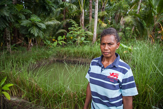 Grace Poporia stands by the family's aquaculture pond, One' Oneabu, Solomon Islands. Photo by Filip Milovac.