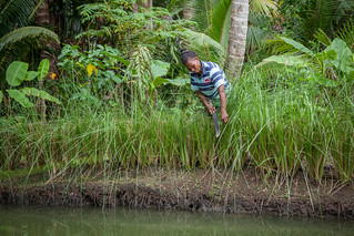 Grace Poporia tends to the grass growing around her aquaculture pond, One' Oneabu village, Malaita Province, Solomon Islands. Photo by Filip Milovac.