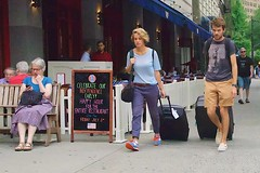 Tourists can't be bothered with Independence Day celebrations (Ed Yourdon) Tags: newyork couple manhattan broadway streetphotography tourists backpack fourthofjuly upperwestside hood peeps independenceday henrys suitcases striding