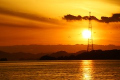 The bright sun and technology (Hal Skygene) Tags: asia japan sun sunset sky water sea seascape waterscape reflection cloud bright light sunlight sunbeam silhouette tower