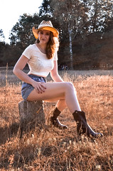 Curiosity (Floris M. Oosterveld) Tags: hot cowgirl girl woman young country sun hat denim shorties shorts hotpants cowboy boots leather straw curious face beautiful cute pretty sexy warm grass nature outside crop top white blue brown rock sitting yellow gold