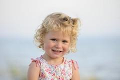 Happy Times (l i v e l t r a) Tags: child d3 70200mmf28g f5 kid portrait happy sunshine curly blonde smile teeth pleased lake blue sky blur bokeh nikkor smiling laugh bows kiddo