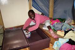 Esther legt fier haar kleren in haar nieuwe kist