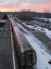 Watching an Amtrak from above as a sunset occurs. (Tim Kiser) Tags: 2014 20140318 amtrak amtrakstation amtraktrain annarbor annarboramtrak annarboramtrakstation annarbormichigan annarborlandscape broadwaystreet broadwaystreetbridge img6781 march march2014 michigan michiganlandscape washtenawcounty washtenawcountymichigan evening eveninglandscape eveninglight landscape orangesky passengertrain railtravel railroadtravel redlights snow snowylandscape southeastmichigan southeasternmichigan sundown sunset sunsetlandscape train trainlights trainplatform trainplatformcanopy trainstation traintravel twolights view viewfromabridge winterlandscape