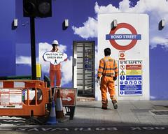 Working Safely Together (stevedexteruk) Tags: street city uk london westminster sign work underground construction crossing cone transport tube signage bond oxfordstreet turnstyle workman